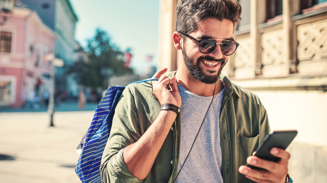 A young man, with a beard and sunglasses, walking through the street, holding a coloured paper over his shoulder,  smiles as he looks at his phone