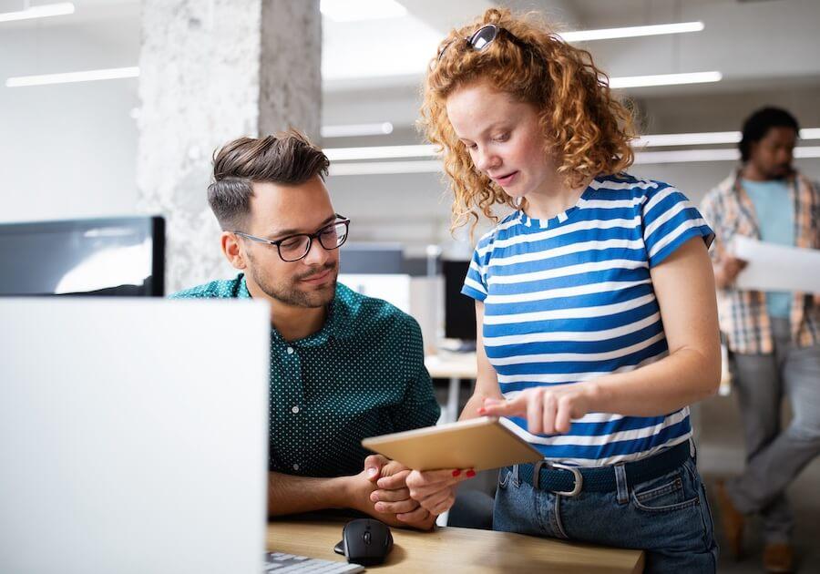 En la oficina, dos jóvenes leen el blog de Cabify en una tablet.