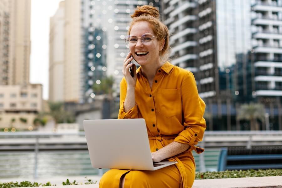 Joven sonriente consulta en el ordenador recursos útiles para su empresa